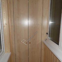 Фотография встроенного шкафа.Крупный план.Двери изготовлены из того же материала, что и все элементы отделки.