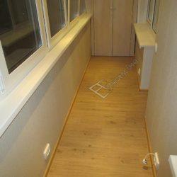 Эта фотография позволяет оценить качество укладки напольного покрытия.Наши мастера использовали качественный линолеум с рисунком под ламинат.Обратите внимание - балкон обшит пластиковыми панелями бежевого цвета.В нижней части стен установлены электрические розетки.